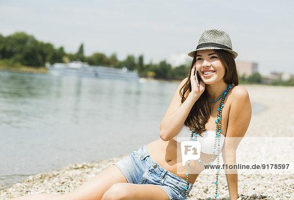 Porträt einer lächelnden jungen Frau beim Telefonieren am Strand