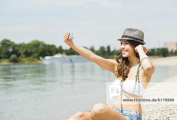 Porträt einer jungen Frau  die einen Selfie mit ihrem Smartphone am Strand nimmt.