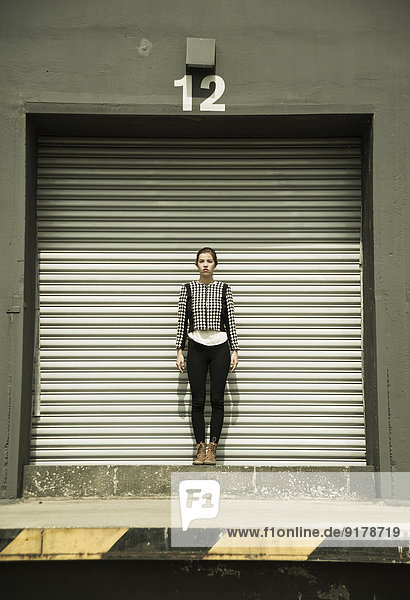 Young woman standing in front of roller shutter