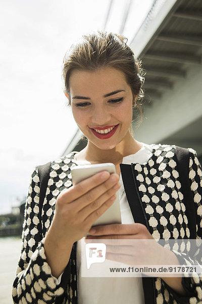 Portrait of smiling young woman with smartphone