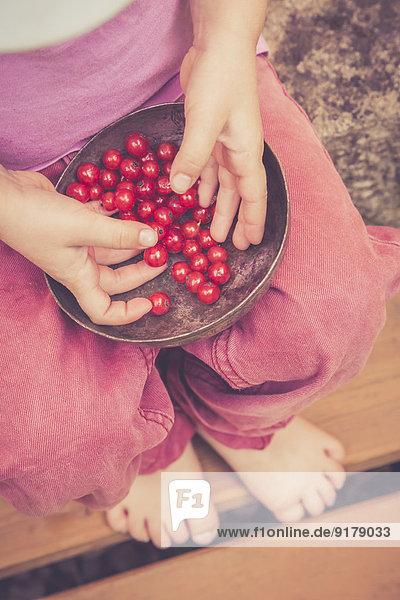 Kleines Mädchen mit Schale mit roten Johannisbeeren  Teilansicht