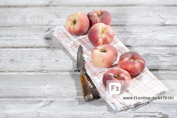 Sechs Donutpfirsiche  Prunus persica var. platycarpa  und ein Messer auf Tuch und Holztisch