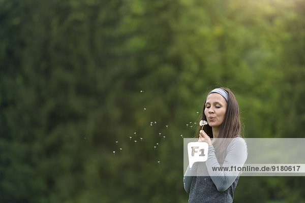 Young woman blowing blowball in front of green background