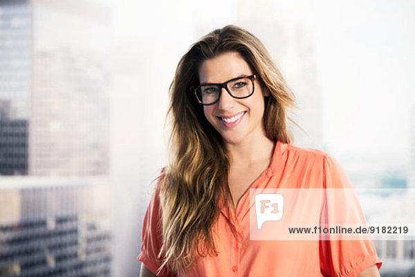 Porträt einer selbstbewussten Geschäftsfrau im Stadtfenster