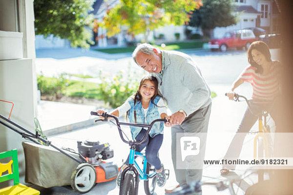 Großvater und Enkelin auf dem Fahrrad in der Garage