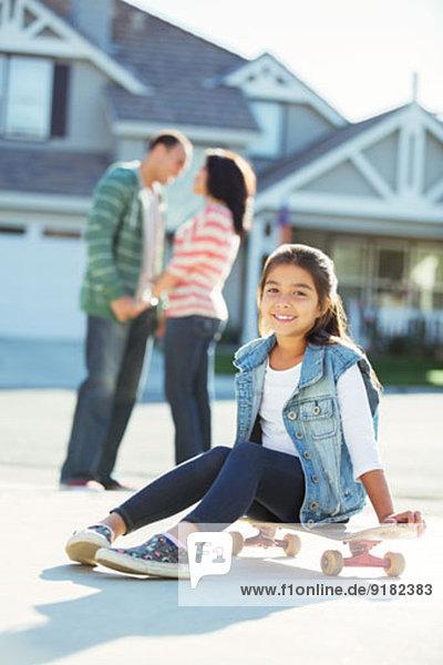 Portrait des lächelnden Mädchens auf dem Skateboard in der Einfahrt