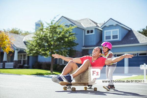 Tochter schiebt Vater auf Skateboard