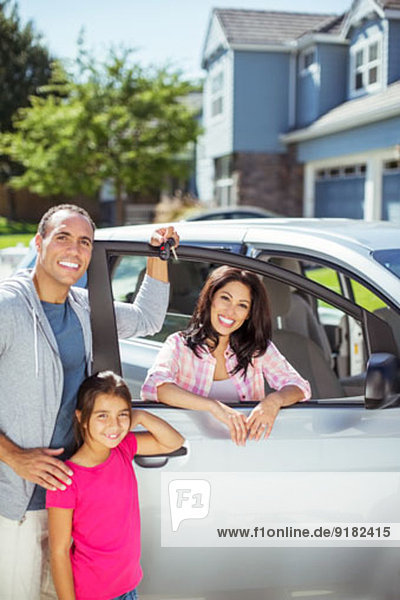 Portrait of smiling family at car in driveway