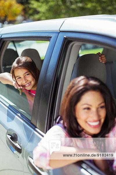 Porträt der lächelnden Mutter und Tochter im Auto