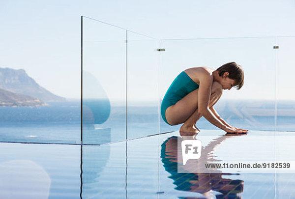 Frau hockt über dem Unendlichkeitspool mit Meerblick
