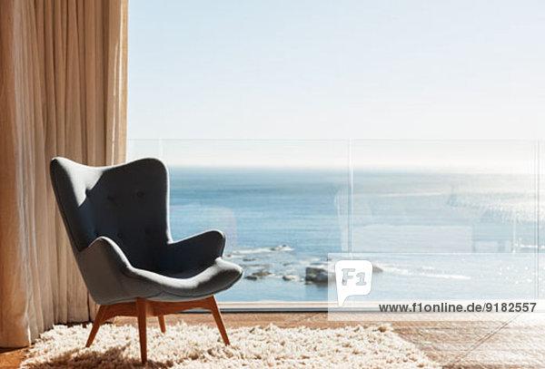 Stuhl im sonnigen Fenster mit Blick aufs Meer