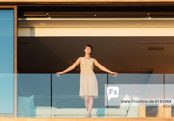Frau steht auf luxuriösem Balkon