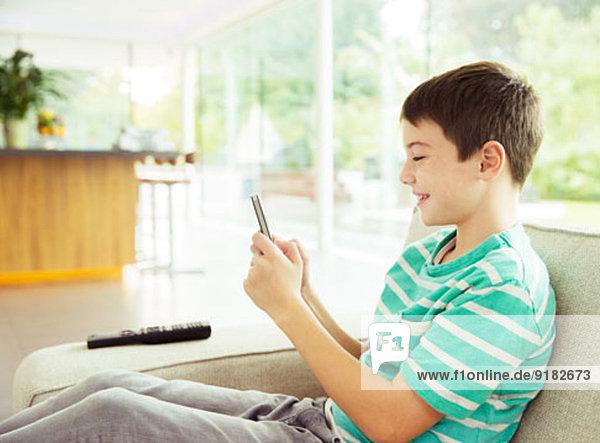 Junge mit Handy auf dem Sofa