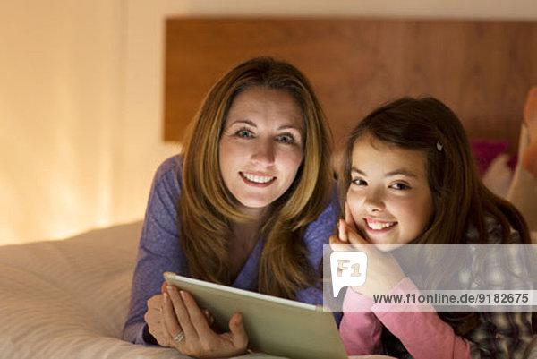 Mutter und Tochter mit digitalem Tablett auf dem Bett