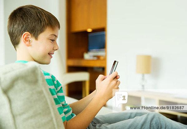 Junge mit Handy im Wohnzimmer