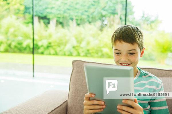 Junge mit digitalem Tablett im Wohnzimmer