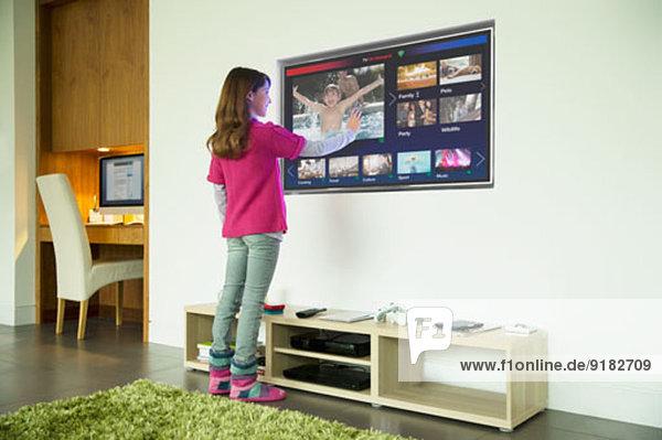 Mädchen mit Touchscreen-Fernseher im Wohnzimmer