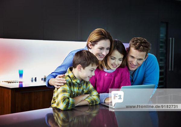 Familie mit Laptop zusammen in der Küche