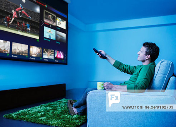 Mann beim Fernsehen im Wohnzimmer