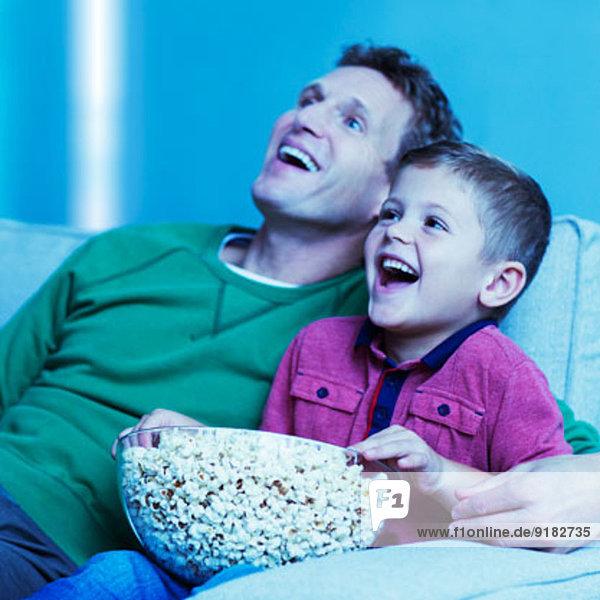Vater und Sohn beim Fernsehen auf dem Sofa