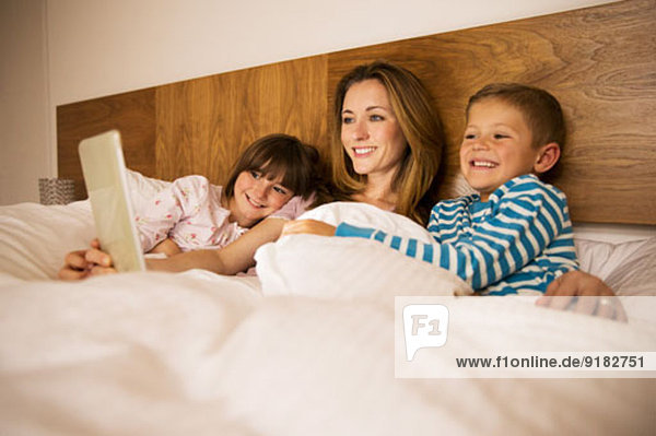 Mutter und Kinder mit digitalem Tablett im Bett