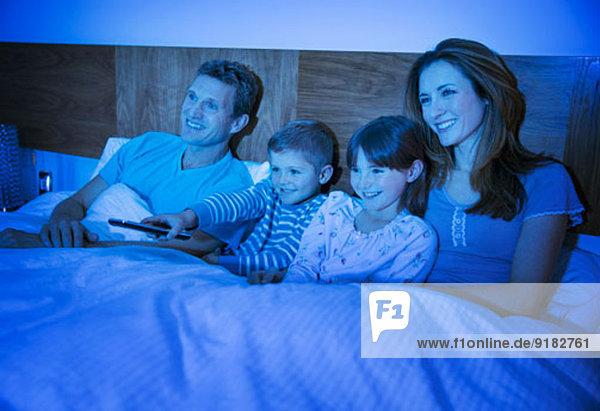 Familie beim Fernsehen im Bett