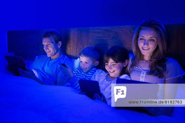 Familie mit Technik im Bett