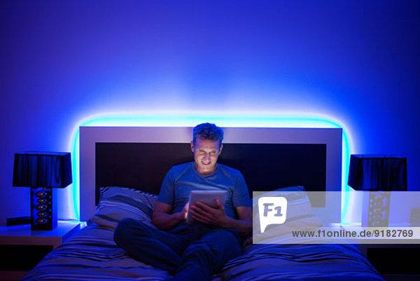 Mann mit digitalem Tablett im Bett