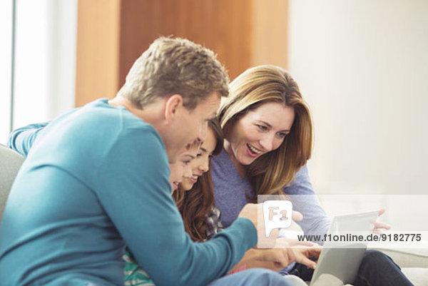 Familie mit Laptop im Wohnzimmer
