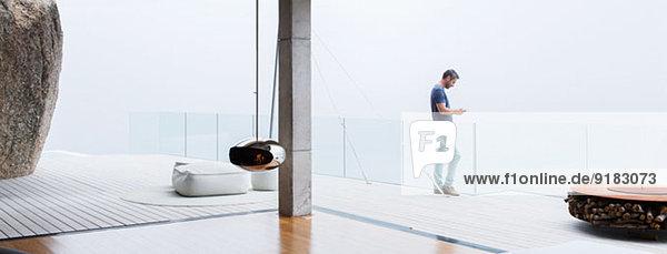 Mann mit Handy auf dem Balkon des modernen Hauses