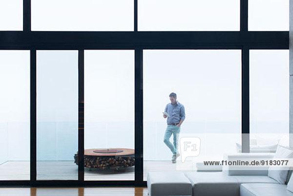 Mann mit Handy auf dem modernen Balkon