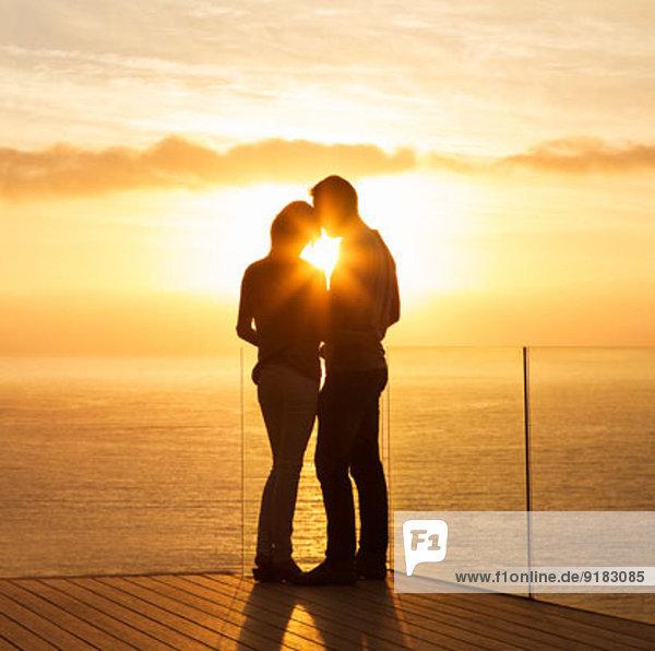 Silhouette des Paares bei Sonnenuntergang über dem Meer