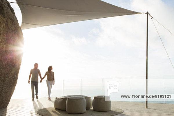 Paar hält Hände auf dem modernen Balkon