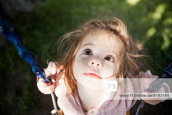 Kleines Mädchen auf der Schaukel im Freien sitzend Kleines Mädchen auf der Schaukel im Freien sitzend