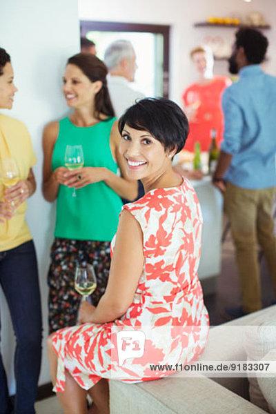Frau lächelt auf dem Sofa auf der Party