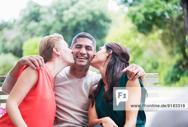 Frauen küssen die Wangen eines Mannes im Freien.