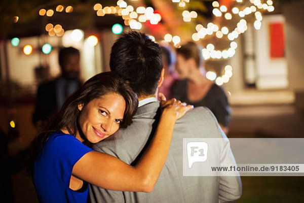 Couple hugging at party