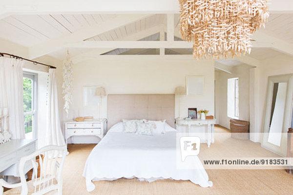 Kronleuchter und Bett im rustikalen Schlafzimmer