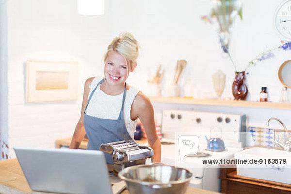Frau am Laptop beim Kochen in der Küche