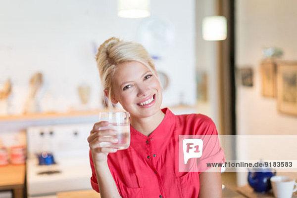 Frau mit einem Glas Wasser in der Küche