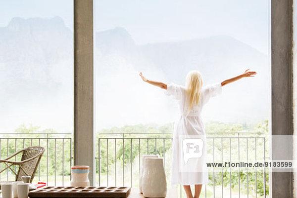 Frau im Bademantel mit Blick auf die Landschaft