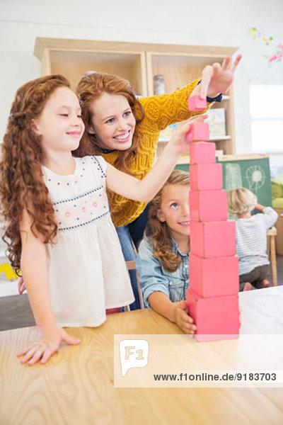 Schüler und Lehrer stapeln Blöcke im Klassenzimmer Schüler und Lehrer stapeln Blöcke im Klassenzimmer