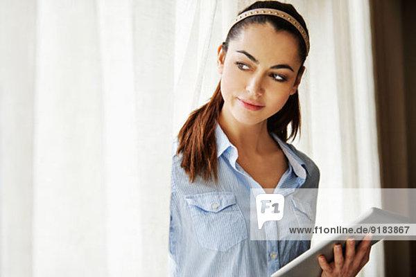Frau mit digitalem Tablett pro Fenster