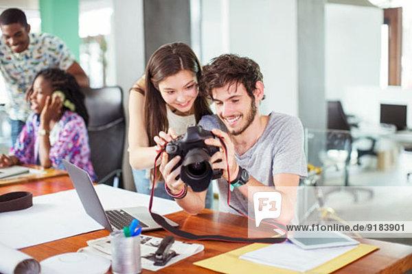 Leute  die gemeinsam im Büro Fotos betrachten.