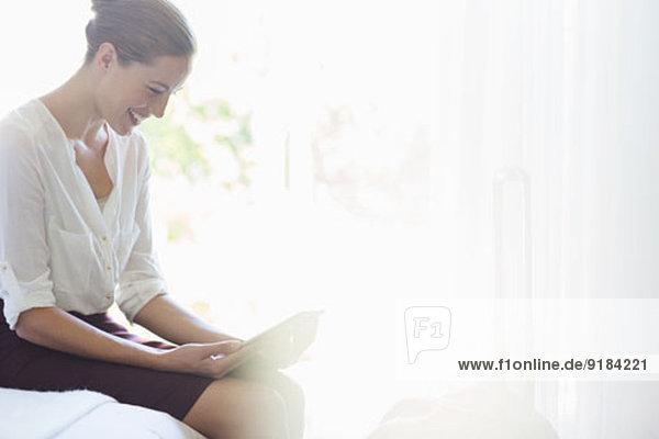 Frau mit digitalem Tablett auf dem Bett