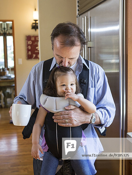 Menschlicher Vater Küche halten Tochter Tragetuch