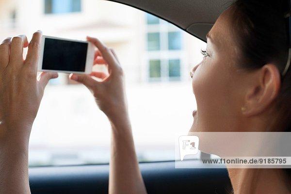 Nahaufnahme einer jungen Frau  die vom Taxifenster aus fotografiert.