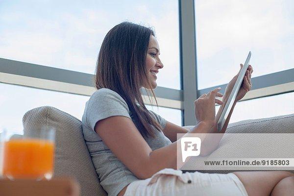 Junge Frau auf Sofa mit digitalem Tablett