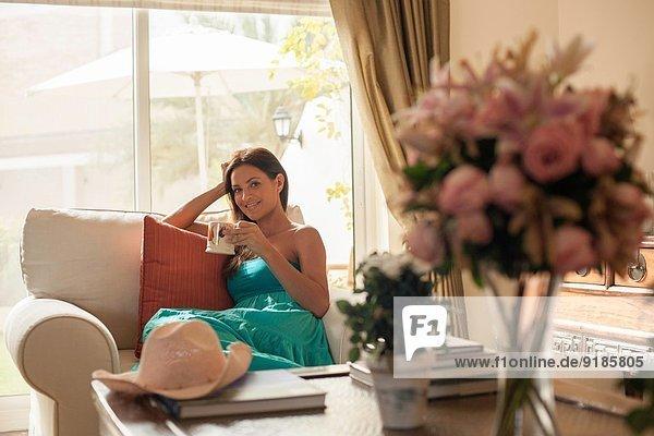 Portrait einer jungen Frau auf einem Sessel mit Kaffeetasse