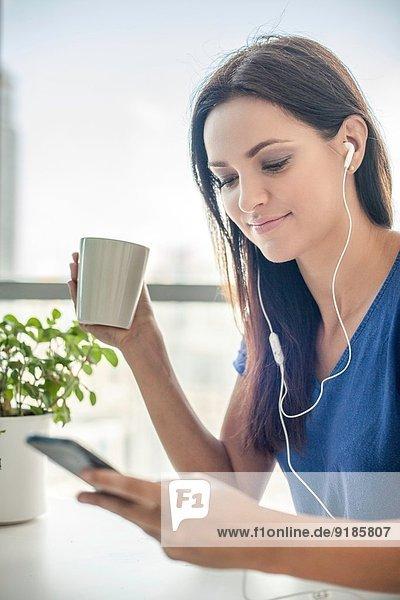 Junge Frau hört Musik auf dem Smartphone